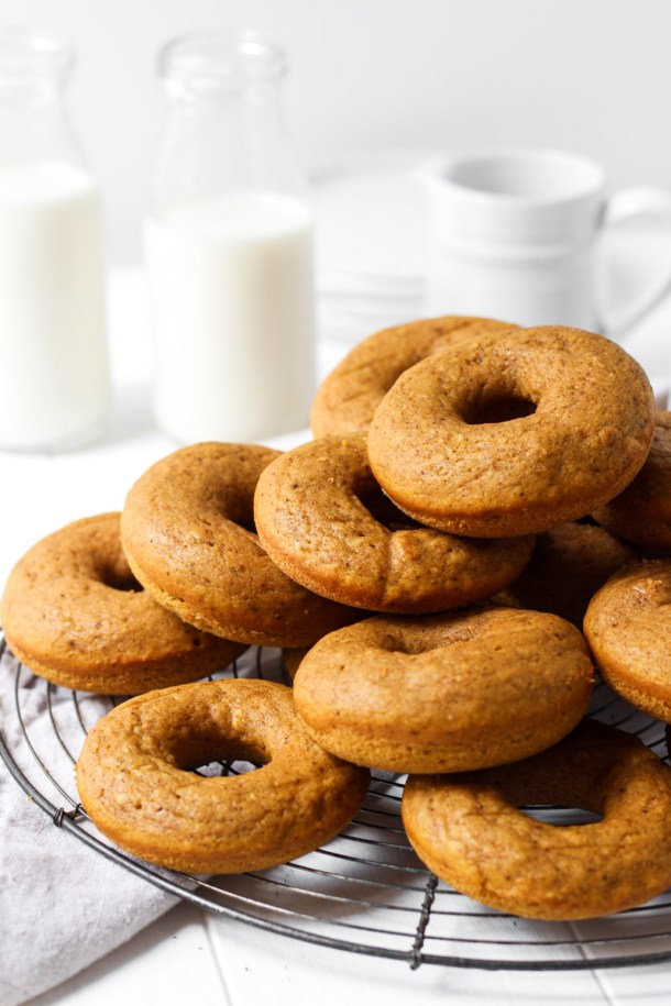 Stack of baked pumpkin donuts on a round French wire rack.