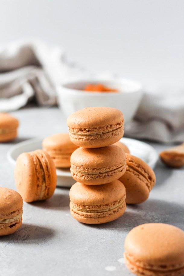 Stack of pumpkin macarons with pumpkin Swiss meringue buttercream.