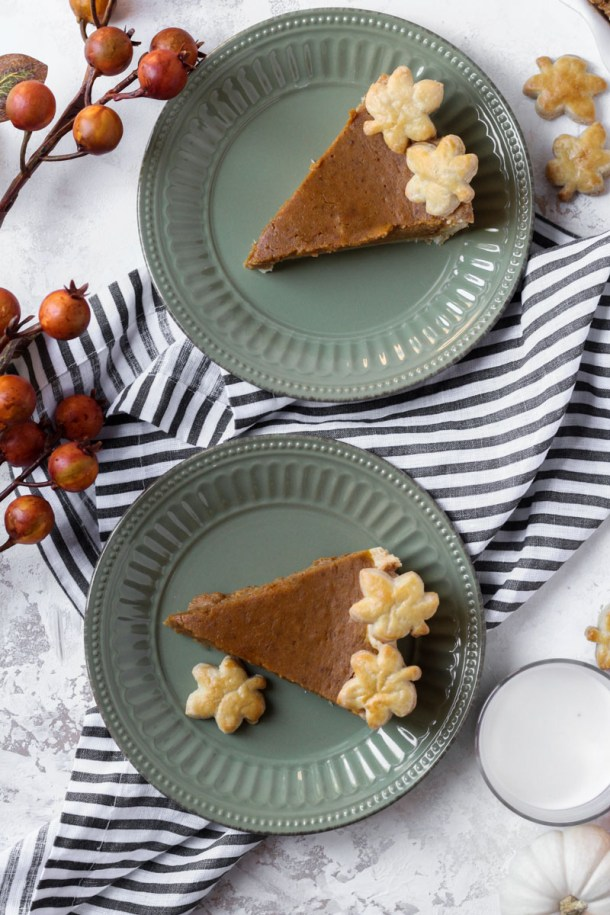 Two slices of brown butter pumpkin pie with pie crust leaf cutouts for a border.