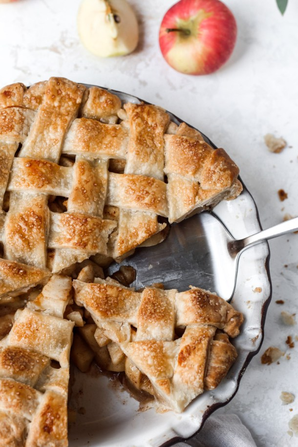 Close up of chai apple pie with a lattice crust and half the pie sliced.