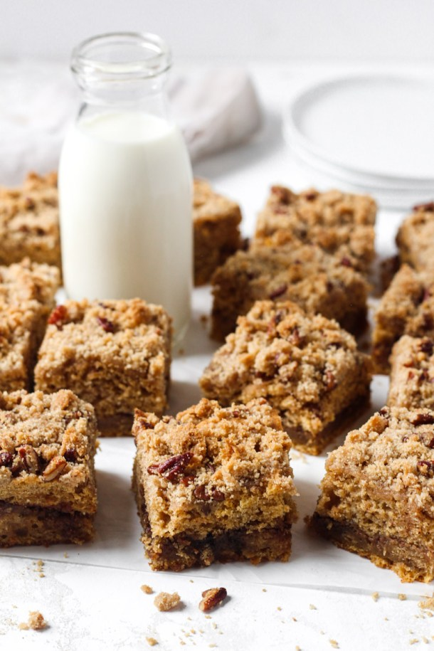 Coffee cake with a sweet potatoes, spiced brown sugar filling, and streusel topping sliced into squares and arranged with a glass of milk.