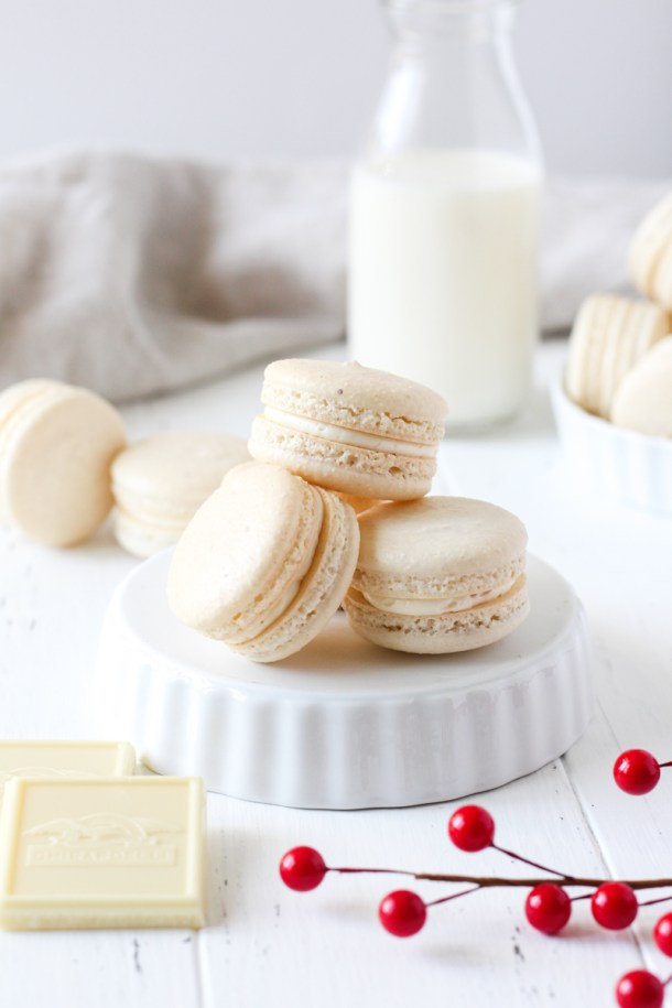 Stack of French macarons filled with cranberry sauce and white chocolate Swiss meringue buttercream on an upside down bowl.