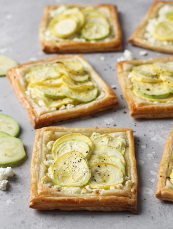 Individual baked puff pastry with feta, zucchini and yellow squash tarts.