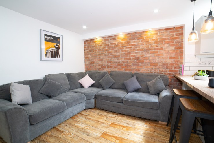 student property in coventry, property photography, brick wall, sofa and art print of berlin with island unit