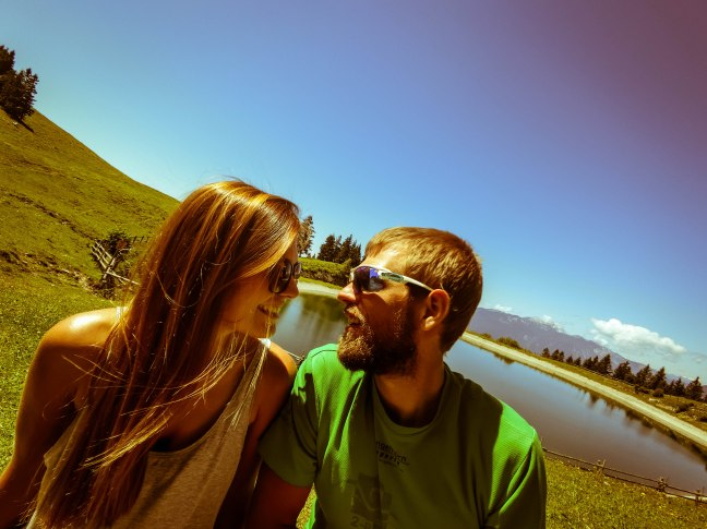 A smiling woman looking at a smiling man in front of a mountain lake