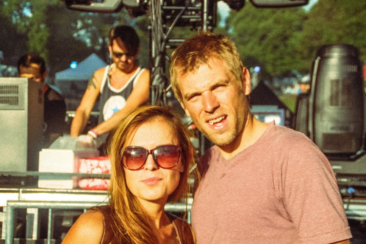 a couple in front of a stage at a music festival