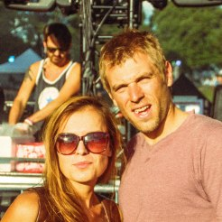 a couple at a music festival in front of a stage with a dj