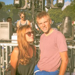 a couple at the Wet music festival in front of a stage with a dj