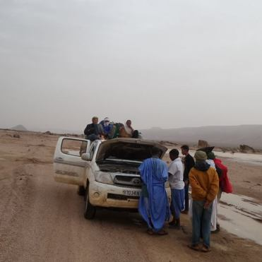 Car breakdown in the desert of Mauritania and men sitting on top / Hitchhiking In West Africa