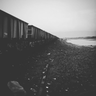 black and white photo of a moving train in the desert / Hitchhiking In West Africa