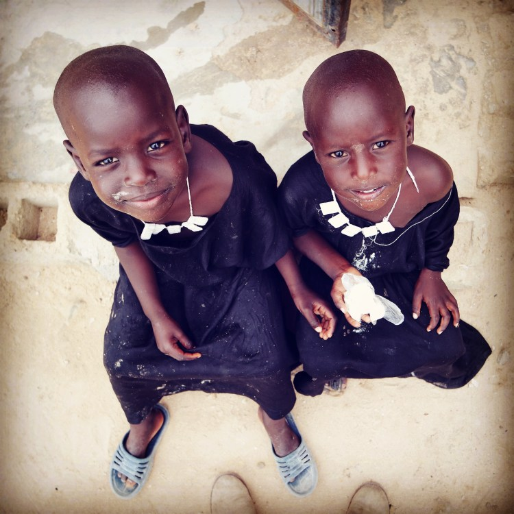 two cute African kids sitting on stones and eat something