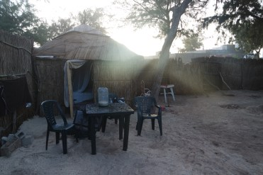 wooden hut with a plastic table and two plastic chairs in West Africa