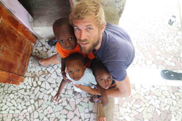 blonde guy with three West African children