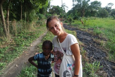 pretty woman in jungle standing next to a African child