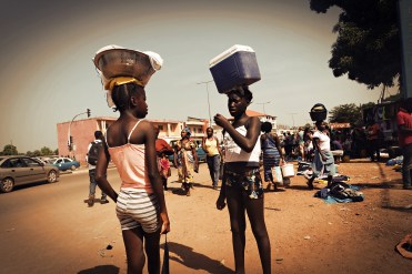 African girls with boxes on their head selling drinks