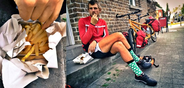 A man eating Belgium French fries on a wall next to tandem bicycle