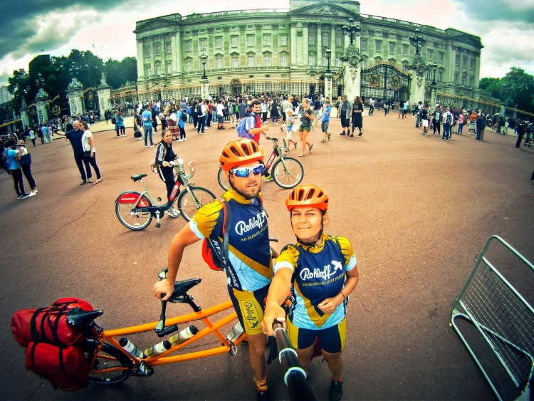 Selfie of a couple with a tandem bicycle in front of the Buckingham Palace, in the United Kingdom