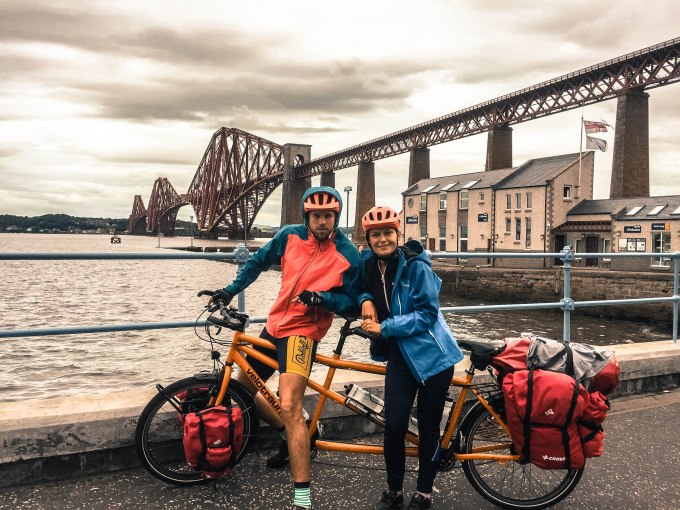 A couple on a tandem bicycle in front of a river and Scottish bridge