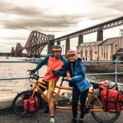 tandem bicycle rider underneath bridge at a river
