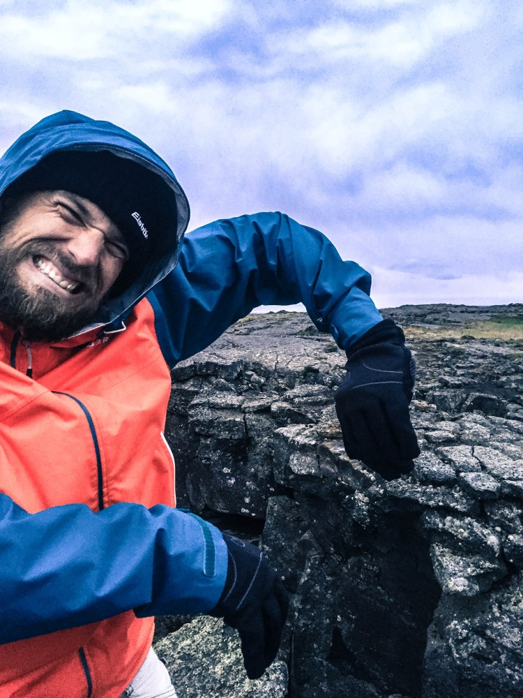 A man pretending to push apart a canyon in Iceland