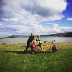 A man and a woman standing next to a tandem bicycle on a fiel in Ireland
