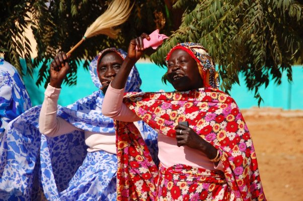 two Bagara tribe women in traditional outfits doing magic in Sudan