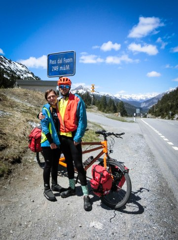 A couple next to a tandem orange Velotraum tandem at the Pass dal Fuorn