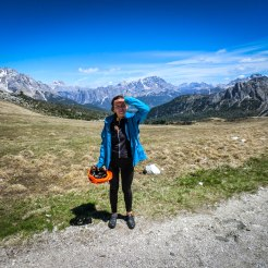 A women holding a bicycle helmet in the mountains
