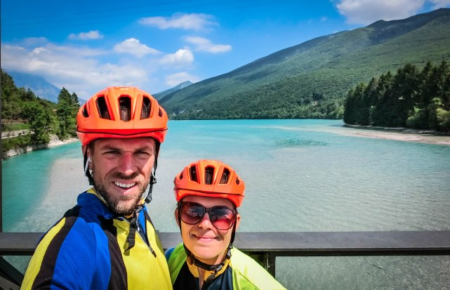 A bicycle couple in front of a crystal clear lake in the Balkans