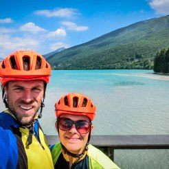 a bicycle couple waering orange helmets in front of a lake
