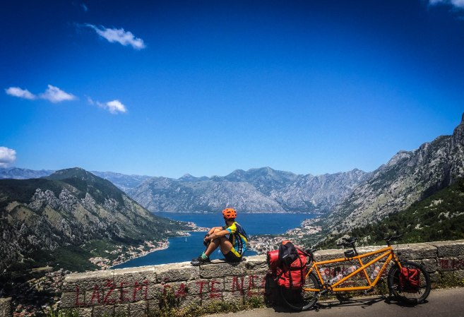 A male cyclist sitting on a wall next to a tandem bicycle in the mountains in front of the mediterranean sea in Montenegro, in the Balkans