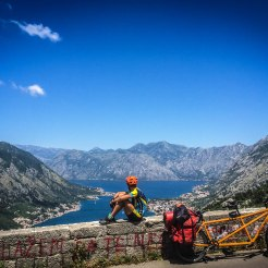a bicycle rider sitting on a wall next to a tandem bicycle in the mountains