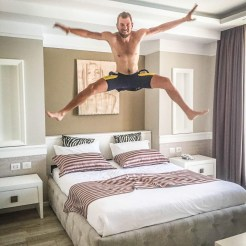A topless man jumping on a bed