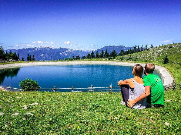 A couple in front of a mountain lake in Slovenia