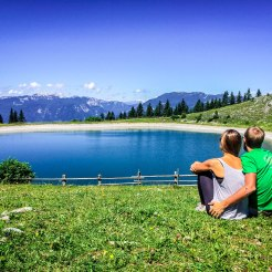 Man hugging woman in front of a mountain lake / How To Stay In Shape While Traveling