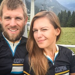 man and women in bicycle jerseys on a cable car