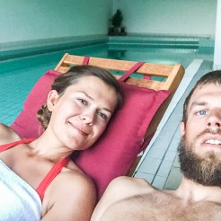 A blonde man and a brunette woman laying on a lounger