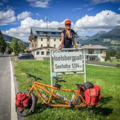 a women on a street sign in front of a tandem bicycle in the mountains
