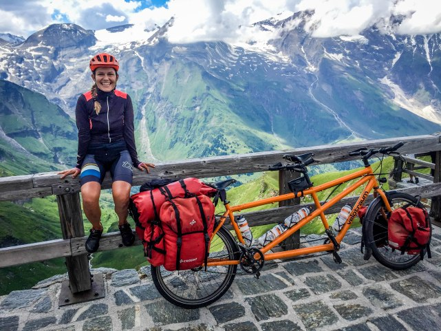 A smiling woman next to a tandem bicycle in the Austrian mountains