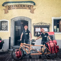 A couple holding a tandem bicycle in front of the Hotel Steinerwirt 1493
