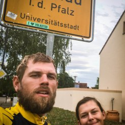 a smiling couple in front if the street sign Landau in der Pfalz