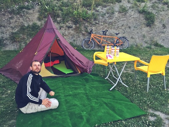 A Blonde german man sitting on a carpet in front of his tent and tandem bicycle in Kosovo during Bicycle Touring On a Budget