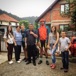 six people next to a tandem bicycle in front of a house in the Balkans