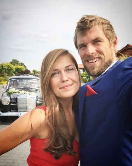 A blonde man wearing a suit and a brunette woman wearing a red dress in front of a car at a wedding