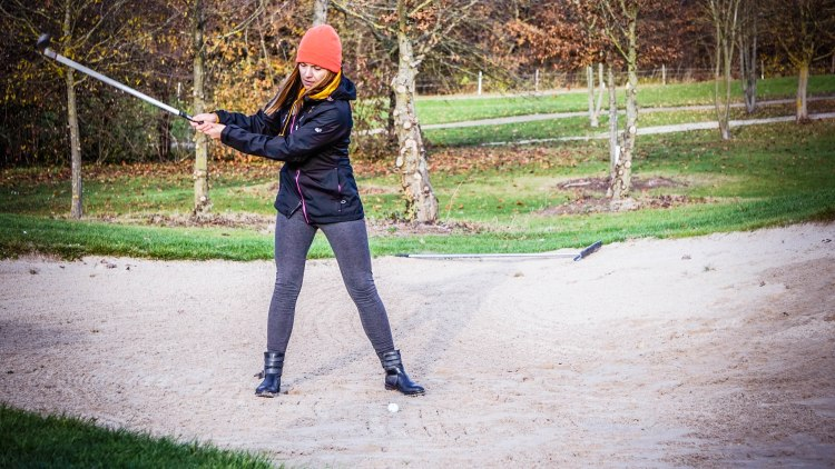 Woman trying to hit a golf ball