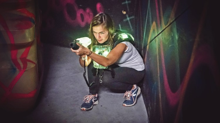 kneeling woman with a lasertag gun