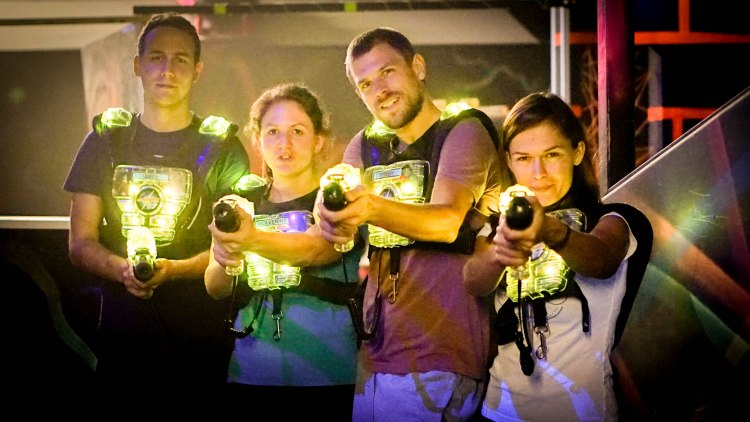 two woman and two man with a lasertag gun