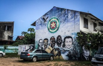 a painting of five people on a building in Cayenne, French Guiana