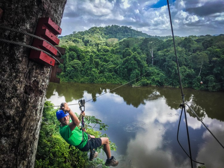 Man doing ziplining in the jungle over a river