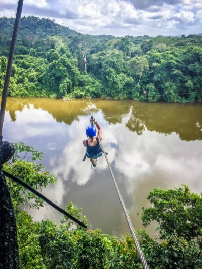 woman doing ziplining in the jungle over a river